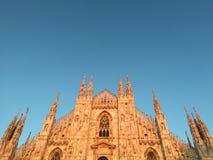 Riflessioni dorate di ora sulla facciata dei Di Milano del duomo Immagine Stock