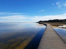 Riflessioni e percorso di legno su laguna della spiaggia di Chia Su Giudeu - Sardegna fotografia stock libera da diritti