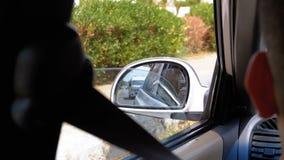 Riflessioni nello specchio laterale dell'automobile che si muove sulla strada al giorno archivi video