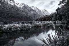 Riflessioni in uno stagno delle montagne innevate nell'isola del sud della Nuova Zelanda in bianco e nero Immagine Stock
