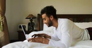 Riflettendo uomo che per mezzo del computer portatile che si trova sulla mattina della camera da letto di Guy Type Chatting Onlin video d archivio