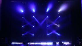 Riflettore blu su una fase vuota di concerto nello scuro Metta in scena gli indicatori luminosi stock footage