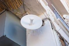 Riflettore parabolico ed antenne della TV sul tetto della casa con il fondo del cielo blu fotografie stock