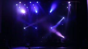 Riflettore variopinto su una fase vuota di concerto nello scuro Liberi la fase con le luci video d archivio