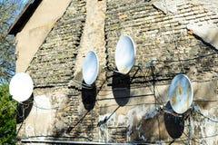 Riflettori parabolici sul vecchio muro di mattoni Telecomunicazione via satellite in Th Fotografia Stock