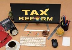 Riforme fiscali con la freccia che va su vista superiore del monitor dell'ufficio Immagini Stock