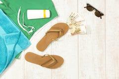 Rifornimenti della spiaggia con soldi su tavola di pavimento Fotografia Stock