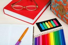 Rifornimenti di banco Istruisca lo zaino, il libro, i vetri, matite di colore, Fotografia Stock