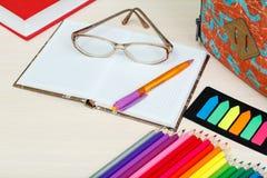 Rifornimenti di banco Istruisca lo zaino, il libro, le matite di colore, taccuino Fotografie Stock