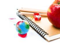 Rifornimenti di scuola con il globo ed il taccuino su fondo bianco Immagine Stock