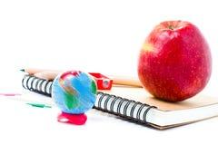 Rifornimenti di scuola con il globo ed il taccuino su fondo bianco Fotografie Stock