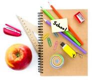 Rifornimenti di scuola con il globo, la mela, le matite ed il taccuino su briciolo Immagine Stock