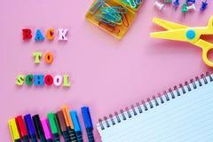 Rifornimenti di scuola con testo di legno DI NUOVO ALLA SCUOLA sul backgrou rosa fotografia stock