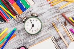 Rifornimenti di scuola differenti: matite, taccuino, indicatori ed insieme degli acquerelli, fondo di legno Fotografia Stock Libera da Diritti