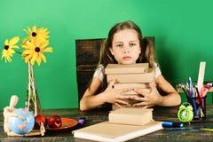 Rifornimenti di scuola e del bambino, fondo verde Ragazza con il fronte annoiato fotografia stock
