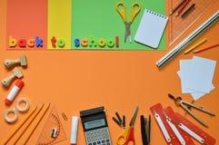 Rifornimenti di scuola e le parole DI NUOVO ALLA SCUOLA Fotografie Stock Libere da Diritti