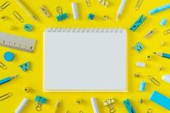 Rifornimenti di scuola multicolori su fondo giallo con lo spazio della copia immagine stock