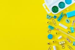 Rifornimenti di scuola multicolori su fondo giallo con lo spazio della copia fotografia stock
