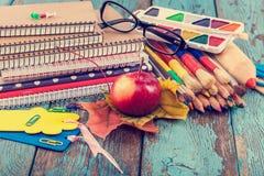 Rifornimenti di scuola o dell'ufficio sulle plance di legno Fotografie Stock