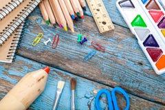 Rifornimenti di scuola o dell'ufficio sulle plance di legno Immagine Stock