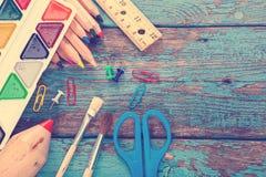 Rifornimenti di scuola o dell'ufficio sulle plance di legno dipinte in blu Fotografie Stock