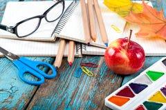 Rifornimenti di scuola o dell'ufficio sulle plance di legno dipinte in blu Fotografia Stock