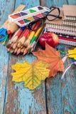 Rifornimenti di scuola o dell'ufficio sulle plance di legno dipinte in blu Immagini Stock