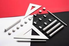 Rifornimenti sulla tavola rossa e nera bianca del fondo Immagini Stock