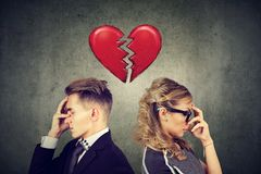 Rift in relations. Sad couple standing back to back with broken heart in-between royalty free stock photo
