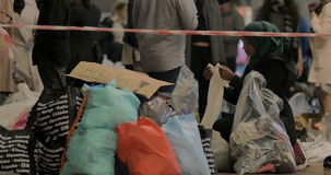 Rifugiato siriano che sceglie i vestiti dei bambini a stock footage