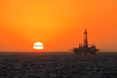 Rig. Sunset with oil drilling rig Stock Image