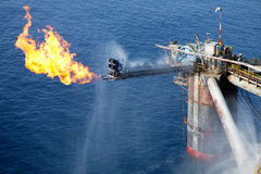 Rig Flaring. Offshore oil rig flaring against a blue sea Stock Photo