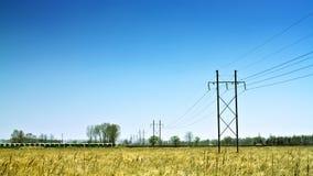Riga ad alta tensione di corrente elettrica nel campo Immagini Stock Libere da Diritti