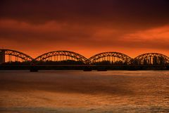 Riga, Daugava railway bridge at sunset. Railway bridge over Daugava river in sunset, Riga, capital city ofLatvia royalty free stock image