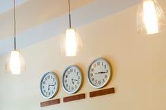 Riga degli orologi che mostrano tempo differente e le lampade Fotografie Stock Libere da Diritti