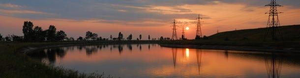 Riga del cavo elettrico lungo il fiume. tramonto. Fotografie Stock Libere da Diritti