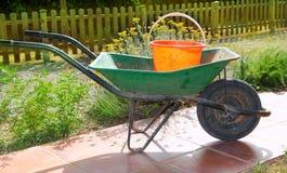 Riga della barra di rotella verde del giardiniere con il secchio arancione Fotografie Stock Libere da Diritti