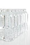 Riga delle bottiglie di acqua di plastica su bianco Immagini Stock Libere da Diritti