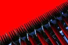 Riga delle forcelle di plastica su colore rosso Fotografia Stock