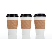 Riga delle tazze di caffè di carta su bianco Immagine Stock