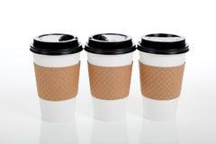 Riga delle tazze di caffè di carta su bianco Immagini Stock