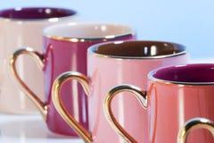 Riga delle tazze di caffè variopinte Fotografia Stock