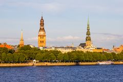 View from Zapadnaya Dvina embankment to Riga Dome Cathedral and St. Peter`s Church Panorama under Rainy Clouds in Sunny royalty free stock photo