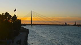 Riga famous cable bridge silhouette aginst dramatic evening twilight sunset sky. Riga Old Town riverside panorama with cable bridge silhouette in evening sunset stock video footage