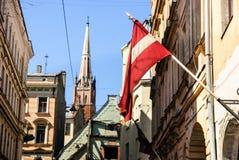 Riga gammal stad med den lettiska flaggan, Riga, Lettland Royaltyfri Foto