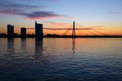 Riga kabel-bliven bro på solnedgången Arkivfoto