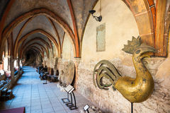 Riga, Latvia - 25-August-2015: old bronze Chicken weathercock. And other ancient artifacts inside the inner courtyard Gallery of Riga Cathedral. Riga, Latvia royalty free stock image
