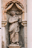 Riga Latvia. Close Ancient Statue Of Man With Bowl On Facade Of St. Peter Church, Stock Photo