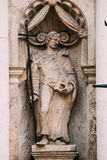 Riga Latvia. Close Ancient Statue Of Man With Cross And Book In Hands On The Facade Of St. Peter Church, Stock Photo