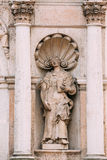 Riga Latvia. Close Ancient Statue Of Woman With Open Book Between Two Pillars On The Facade Of St. Peter Church, Royalty Free Stock Photography
